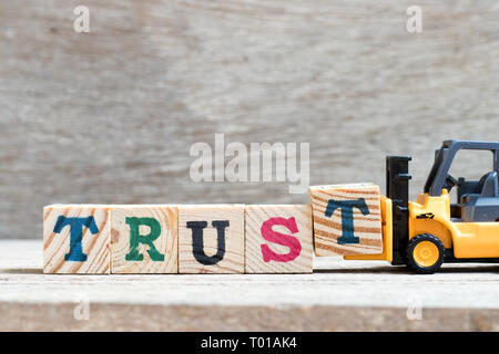 Toy forklift hold letter block t to complete word trust on wood background - Stock Photo