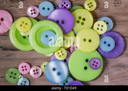 pile of pastel coloured buttons on a wooden background - Stock Photo