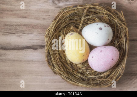 Three chocolate eggs in a nest, resting on a wooden background - Stock Photo