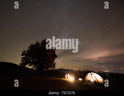 Company of tree tourists hikers, men and women having a rest by burning bonfire near illuminated tent and big tree in the mountains, enjoying beautifu - Stock Photo