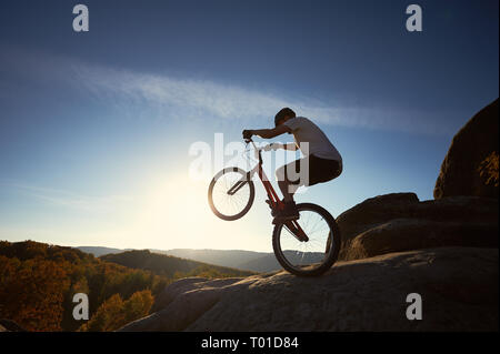 Sportsman cyclist standing on back wheel on trial bicycle, man biker balancing on the top of mountain in the summer sunny morning. Blue sky and sunris - Stock Photo