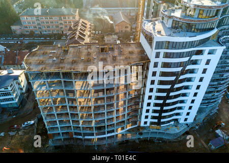 Tall multi storied modern apartment or office building with shiny windows and unfinished building under construction. - Stock Photo