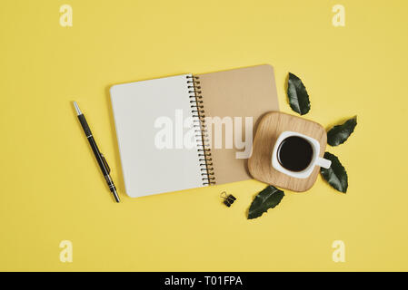 Yellow office desk table with blank notebook, green leaf, pen, supplies and coffee cup. Flat lay, top view with copy space. Stylish female concept. - Stock Photo