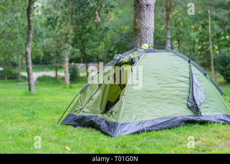 Small green tent pitched near tree on camping in rural England.Tourism in UK.Outdoors equipment.Vacation on British countryside.Holidays.Relaxation. - Stock Photo