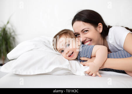 mother and baby boy on bed - Stock Photo