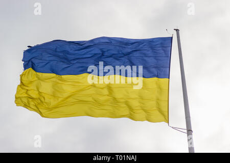 The flag of Ukraine flutters in the wind on a high flagpole in Dnipro city. Shooting at close range. Real flag in windy afternoon. Independence symbol - Stock Photo