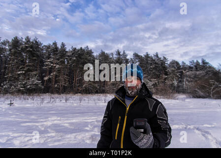Good-natured bearded man with a snowy beard, slight smile and GPS navigator is standing on the edge of a taiga forest - Stock Photo
