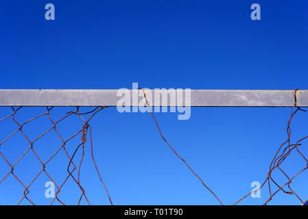 Broken and damaged chainlink mesh wire fence with a blue sky and a whole in the fencing - Stock Photo