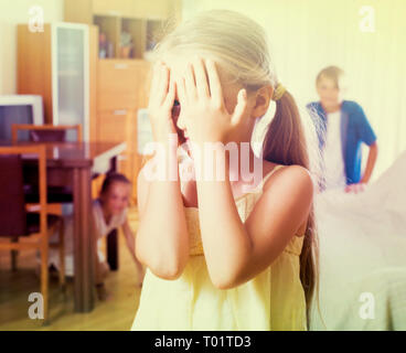 Teenage boy with little sisters playing hide-and-go-seek in living room - Stock Photo