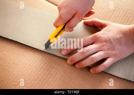 Paper knife in person hands cutting cardboard. Close-up. - Stock Photo