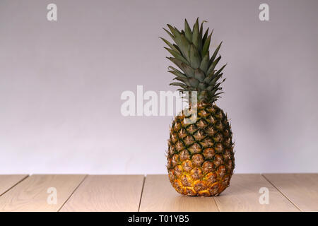 The composition of the whole pineapple on a light background. - Stock Photo