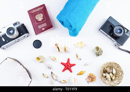 Seashells and camera on white background, passport, travel - Stock Photo