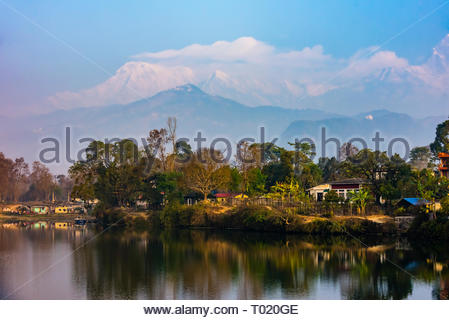 Peaks of the Annapurna Massif of the Himalayas tower above Phewa Lake in Pokhara, Nepal. - Stock Photo