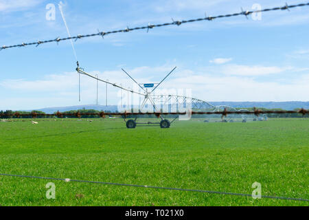 On other side of barbed wire fence a large centre pivot irrigation system running on a farm in Central Otago, New Zealand providing water distribution - Stock Photo