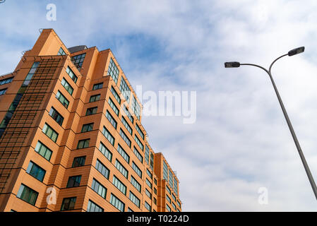 Business center. Red brick building with green windows against the sky. - Stock Photo