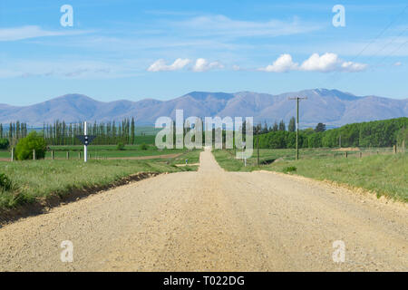 Long dry gravel country road ahead stretching in distance through farmland with distant hills under blue sky with cloud. - Stock Photo