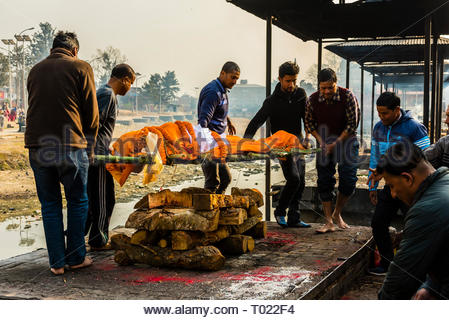 A corpse is prepared for cremation on the funeral pyre. Pashupatinath Temple, a Hindu temple along the Bagmati River in Kathmandu, Nepal. The Bagmati  - Stock Photo