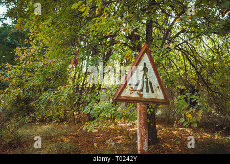 Old rusty, frayed, scratched red triangular traffic sign - pedestrian crossing in radioactive zone in Pripyat city. Chornobyl exclusion zone - Stock Photo
