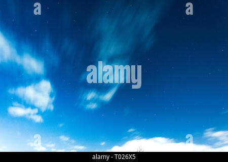 Electric blue night sky with bright stars and passing clouds somewhere in London. - Stock Photo