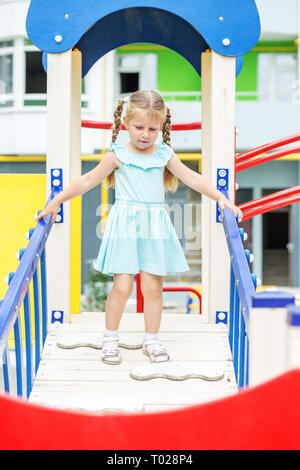 Little cheerful girl plays on the playground. The concept of childhood, lifestyle, upbringing, kindergarten - Stock Photo