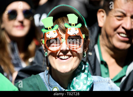 Beijing, USA. 16th Mar, 2019. A woman watches the St. Patrick's Day Parade in New York, the United States, on March 16, 2019. Hundreds of thousands of people gathered along New York's Fifth Avenue to watch the St. Patrick's Day Parade on Saturday. The St. Patrick's Day is marked on March 17. Credit: Wang Ying/Xinhua/Alamy Live News - Stock Photo