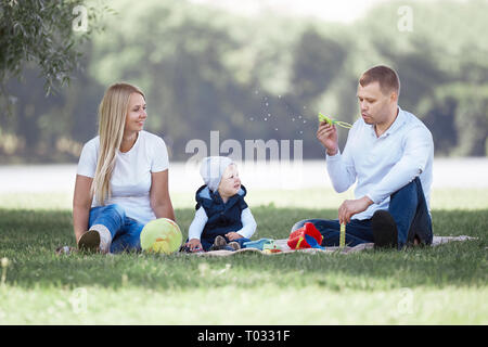 parents and their little son blowing bubbles on a summer day walk. - Stock Photo