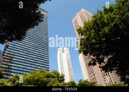 Tall buildings towering over trees in Tokyo, Japan - Stock Photo