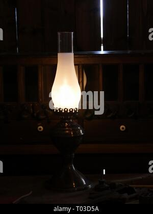 Lighted antique oil lamp in a dark room with wooden walls - Stock Photo