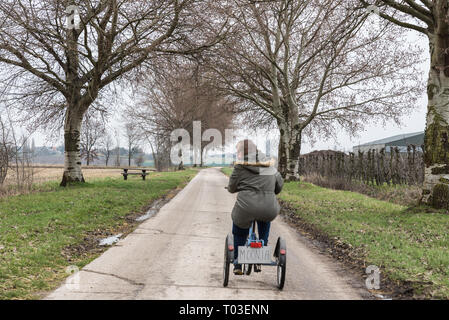Hakendover, Flanders / Belgium - 03 02 2019: Young white woman with Down Syndrome drive a tricycle at the Suikerroute the Sugar bicycle trail at the B - Stock Photo