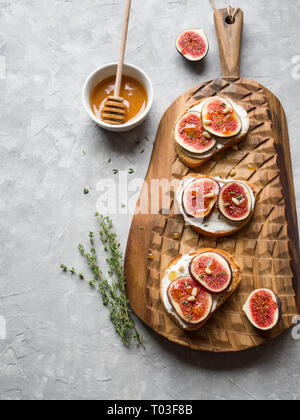 Three toasts with ricotta and figs with honey thyme and pine nuts on a board on a gray background - Stock Photo