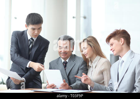project Manager and business team use a digital tablet to obtain operational information - Stock Photo