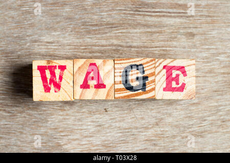 Letter block in word wage on wood background - Stock Photo