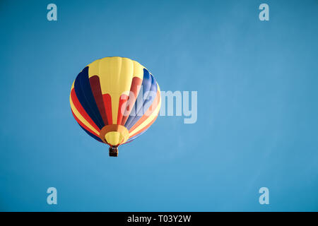 Colorful hot air balloon up in the dark blue sky. - Stock Photo