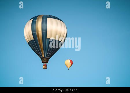 Two hot air balloons in the clear blue sky during a festival. - Stock Photo