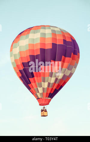 Red and purple hot air balloon floating in the clear sky. - Stock Photo