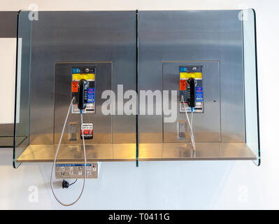 2 Payphones side by side hanging on a wall in Chantilly VA - Stock Photo