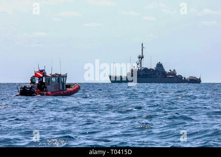 190314-N-AD347-1133 PHILIPPINE SEA (March 14, 2019) Marines assigned to 3rd Reconnaissance Battalion work with the Avenger-class mine countermeasures ship USS Pioneer (MCM 9) to conduct a mine hunting training exercise. Pioneer, part of Mine Countermeasure Squadron 7, is operating in the U.S. 7th Fleet area of operations to enhance interoperability with partners and serve as a ready-response platform for contingency operations. (U.S. Navy photo by LTJG Alexander Fairbanks) - Stock Photo