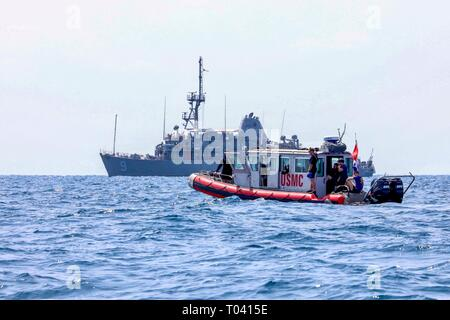 190314-N-AD347-1152 PHILIPPINE SEA (March 14, 2019) Marines assigned to 3rd Reconnaissance Battalion work with the Avenger-class mine countermeasures ship USS Pioneer (MCM 9) to conduct a mine hunting training exercise. Pioneer, part of Mine Countermeasure Squadron 7, is operating in the U.S. 7th Fleet area of operations to enhance interoperability with partners and serve as a ready-response platform for contingency operations. (U.S. Navy photo by LTJG Alexander Fairbanks) - Stock Photo