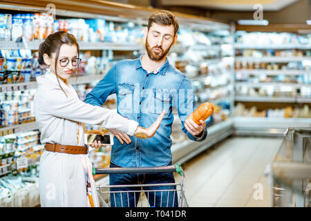 Man choosing sausages, standing with his dissatisfied wife in the supermarket - Stock Photo
