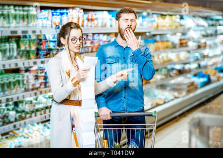 Young couple buying food standing with cart and long shopping list in the supermarket - Stock Photo