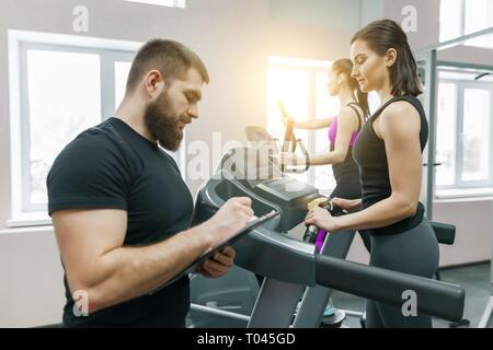 Young smiling fitness women with personal trainer an adult athletic man on treadmill in the gym. Sport, teamwork, training, healthy lifestyle concept.