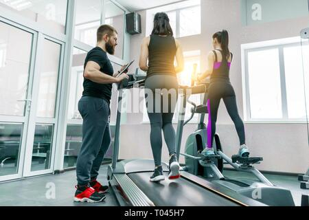 Young athletic women on treadmill, personal instructor coaching and helping client woman. Fitness, sport, training, people concept