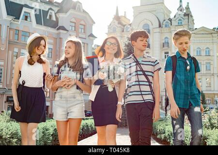 Outdoor portrait of school teacher with bouquet of flowers and group of teenage school children. Children congratulate their teacher, teacher's day - Stock Photo