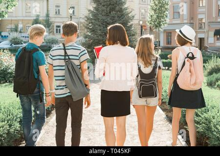 Outdoor portrait of school teacher and group of teenagers high school students. Children walking with teacher, view from the back. - Stock Photo