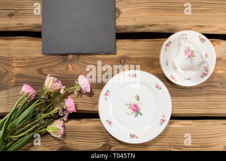Slate board on rustic wood planks background with romantic porcelain and flowers. For cafés, menu concept, banner, safe the date, wedding. - Stock Photo
