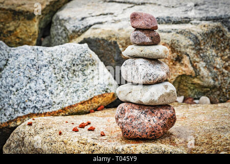 Six stones stacked on top of each other. These stacked stones are also known as Cairn - Stock Photo