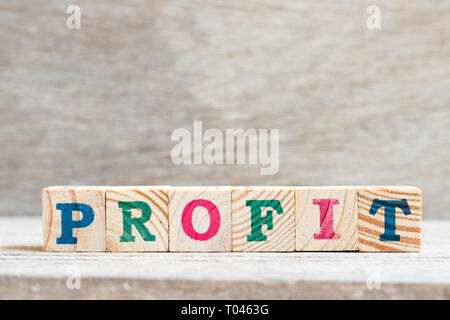 Letter block in word profit on wood background - Stock Photo