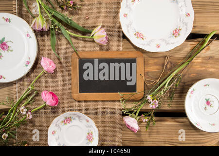 Old fashioned chalkboard/blackboard on rustic wood planks background with romantic porcelain and flower arrangement. Mother's day, Valentines day. - Stock Photo