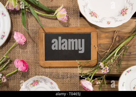 Old chalkboard slate on rustic wood planks background with romantic porcelain and flowers. For cafés, menu concept, banner, safe the date, wedding. - Stock Photo