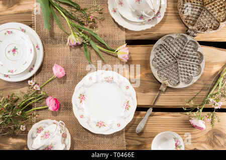 Old romantic porcelain, pink flowers and ancient waffle iron arranged on rustic wood planks. Shot from above, flat lay. - Stock Photo
